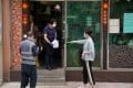 A staff member wearing a face mask hands takeaway food to a customer outside a restaurant in Hong Kong. Photo: Reuters