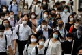 Commuters and passers-by wearing protective face masks in Tokyo. Photo: Reuters
