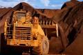 Excavators move iron ore at Port Hedland in Australia. Photo: Bloomberg