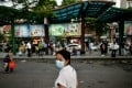 A woman wearing a face mask waits at a bus stop in Hanoi on July 29. Photo: AFP