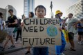 A boy holds a sign during a climate change strike outside a park in Bangkok on November 29, 2019. Photo: EPA-EFE