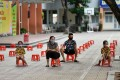 A family sit on plastic stools as they wait to be tested at a makeshift rapid testing centre for coronavirus in Hanoi. Photo: AFP