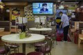 A restaurant employee cleans the floor as a television broadcasts Hong Kong Chief Executive Carrie Lam explaining her decision to postpone the Legco elections. Photo: AP