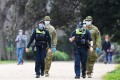 Police officers and soldiers patrol a popular running track in Melbourne on Tuesday. Photo: Agence France-Presse