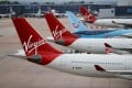 FILE PHOTO: Virgin Atlantic and TUI Airways aircraft are seen at Manchester Airport, following the outbreak of the coronavirus disease (COVID-19), Manchester, Britain, June 8, 2020. REUTERS/Phil Noble/File Photo