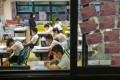 Students and teachers at S.K.H. St. James' Primary School in Wan Chai pray for an easing of the coronavirus situation in Hong Kong as classes resumed in late June. A return to online learning was only about a month away. Photo: Nora Tam