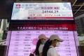 Women walk past a bank's electronic board showing the Hong Kong share index at Hong Kong Stock Exchange. Photo: AP