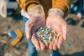 Detail of hands showing microplastics on the beach. Photo: Shutterstock