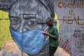 A boy wearing a face mask carries a small bowl of githeri, or mixed beans and maize, as he walks past an informational mural warning people about the risk of the new coronavirus, painted by graffiti artists from the Mathare Roots youth group, in the Mathare slum, or informal settlement, of Nairobi, Kenya Saturday, in April 2020. Photo: AP