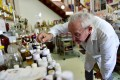 """Geneticist and """"aroma sculptor"""" Michael Moisseeff examines items in his laboratory in Montegut-Lauragais near Toulouse, southwestern France, in July. Photo: AFP"""