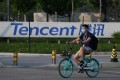 Tencent's second-quarter net income beat expectations. Here, a man bikes past a sign for Tencent in Beijing. Photo: Agence France-Presse