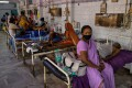 A woman sits on a hospital bed in Bhagalpur while her husband, a Covid-19 patient, waits to be transferred to ICU. Medical experts say India will reach 3 million cases in the next 10 days. Photo: Reuters