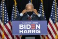 Democratic presidential candidate Joe Biden removes his face mask as he prepares to speak at the Hotel DuPont in Wilmington, Delaware, on Thursday. Photo: AP