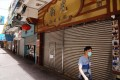 A man in a face mask walks past a closed restaurant in Wan Chai amid the third wave of coronavirus infections. Photo: SCMP / Sam Tsang