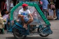 A rickshaw driver wears a face mask and a makeshift face shield made of a water bottle, following their mandatory use in all public transport, amid the coronavirus outbreak in Manila, Philippines. The worst impacts of the pandemic have been felt by informal workers, migrant workers and the poor. Photo: Reuters