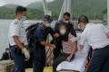 Rescuers helping the elderly woman after she was taken to shore in Sai Kung. Photo: Handout