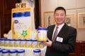 Leng Youbin, chairman of China Feihe, highlights one of its range of milk products during a media briefing on its IPO in Hong Kong October 2019. Photo: China News Service via Getty Images