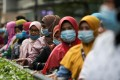 Women queue at a bus station in Kuala Lumpur, Malaysia. Photo: Reuters