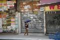 A woman walks past a row of closed shops in Tsim Sha Tsui. Photo: Felix Wong