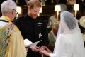 Britain's Prince Harry, Duke of Sussex, places the wedding ring on the finger of Meghan Markle during their wedding in St George's Chapel, Windsor Castle in 2018. Photo: AFP