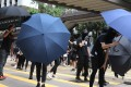 Anti-government protesters open their umbrellas as police approach during an unlawful demonstration on July 1, the anniversary of Hong Kong's handover from British to Chinese sovereignty. Photo: K. Y. Cheng