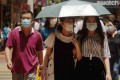 Pedestrians use an umbrella to shield themselves from the sun as they walk down the street on Monday. Photo: Sam Tsang
