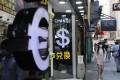 Symbols for the euro and US dollar at currency exchange booths in Tsim Sha Tsui, Hong Kong. Photo: Sam Tsang