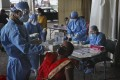 Health workers conduct Covid-19 antigen tests for migrant workers in New Delhi, India. Photo: AP