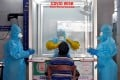 A doctor in a protective chamber takes a swab to test for Covid-19, at a newly installed walk-in sample kiosk at a government-run hospital in the southern Indian city of Chennai on April 13. Photo: Reuters