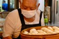 Wu Huang-yi, 80, brings out fresh baskets of guabao at his stall in Taipei's Huaxi Street Night Market. Photo: AFP