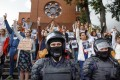 Riot police block protesters in front of a church in Minsk, Belarus on Thursday. Photo: AP