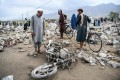Residents gather among debris after a flash flood affected the area at Sayrah-e-Hopiyan in Charikar, Parwan province. Photo: AFP