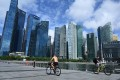 Cyclists pedal down the Marina Bay promenade, flanked by skyscrapers housing banks and other financial institutions, in Singapore. Photo: AFP