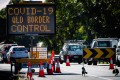 Covid-19 signage at a vehicle checkpoint on the Pacific Highway on the Queensland-New South Wales border in Brisbane on April 15. Photo: AFP