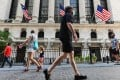 People pass by the New York Stock Exchange on Wall Street in New York City on August 3. Wall Street flexed its muscles on August 28, with the Dow erasing its losses for the year and the S&P and Nasdaq again hitting records as investors shrugged off the ongoing coronavirus crisis. Photo: AFP