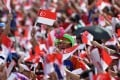 A young Singaporean joins the crowds in waving the country's flag during National Day celebrations on August 9, 2017. Photo: AFP