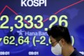 A currency trader walks by the screen showing the Korea Composite Stock Price Index at the foreign exchange dealing room in Seoul. Photo: AP