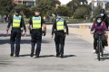 Protective services officers patrol along the St Kilda Beach foreshore in Melbourne as the city battles an outbreak of the coronavirus. Photo: AFP