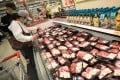 Shoppers examine pork for sale at a Wellcome supermarket in Causeway Bay in April. Photo: May Tse