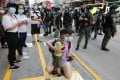 A woman holds a child in Mong Kok as police officers stand ready to prevent anti-government protesters gathering to rally on September 6. Photo: May Tse