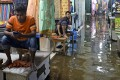 Shopkeepers wait for customers in a waterlogged shopping centre after a heavy downpour in Dhaka, Bangladesh, on July 21. Climate-change issues are rising on Asia's economic and social agenda. Photo: AFP