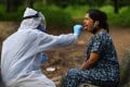 A medical staff takes a nasal swab sample from a woman outside a quarantine centre in Nashik, India. Photo: AFP
