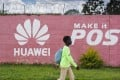 A pedestrian passes the Huawei logo painted on a wall in Lusaka, Zambia, on December 11, 2018. Many digital infrastructure projects in Zambia, like the more visible airport terminals and highways, are being built and financed by China. Photo: Bloomberg