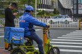 A Ele.me delivery driver waits to cross the pedestrian crossing in the Futian district in Shenzhen, 2019. Photo: SCMP/Roy Issa