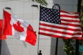 US and Canada flags fly in Detroit. The US said last month that an influx of Canadian aluminium was the reason for a 10 per cent tariff. Photo: Reuters