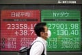 A man walks by screens showing Japan's Nikkei 225 index and the Dow Jones Industrial Average at a securities firm in Tokyo on September 18. Photo: AP