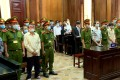 Defendants from the Trieu Dai Viet group stand between policemen during their trial over terrorism activities at a court in Ho Chi Minh City. Photo: Reuters