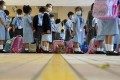 Children wait to have their temperatures checked at Yaumati Catholic Primary School (Hoi Wang Road). Photo: Winson Wong
