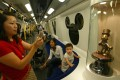 Visitors take photos on a Disneyland Resort Line train on the first day of its operation in August 2005. The theme park, which opened a month later and is majority-owned by the Hong Kong government, has struggled for years. Photo: SCMP