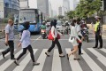Jakarta residents wearing face masks as a precaution against Covid-19 cross the road in the capital's central business district. Photo: AP